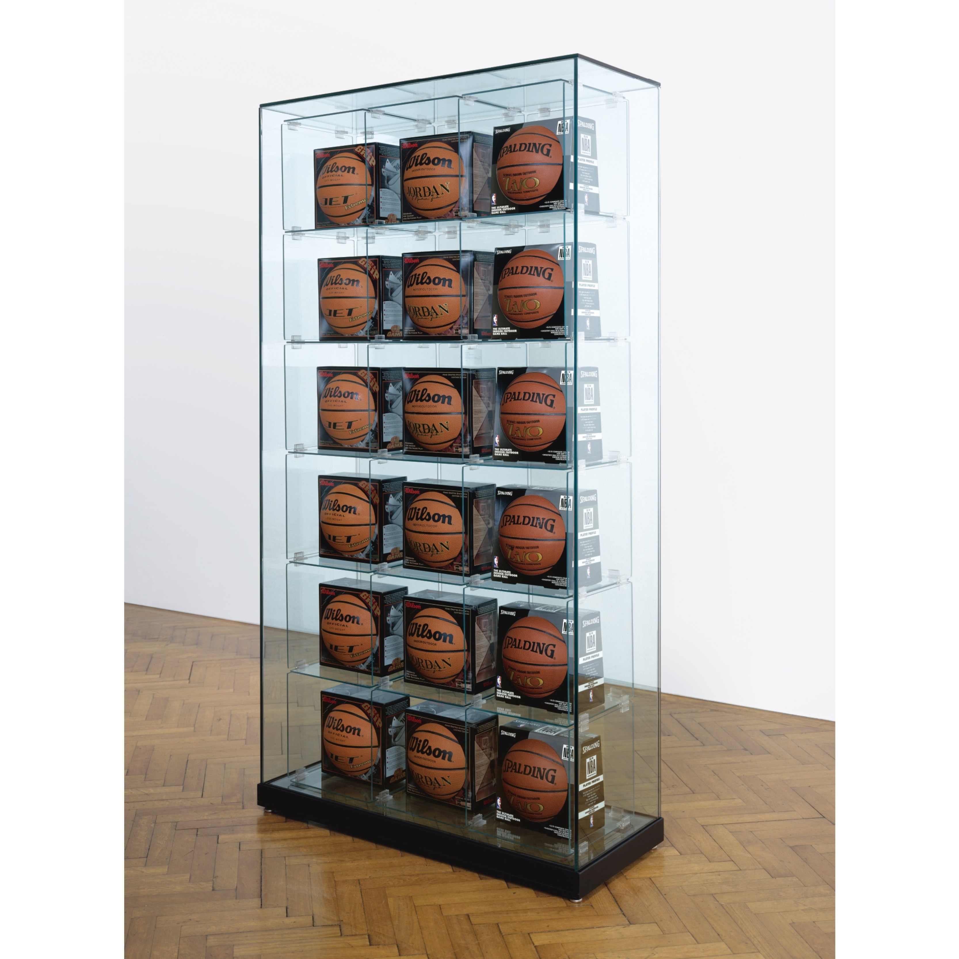 JEFF KOONS Encased - Three Rows (6 Wilson Jet Basketballs, 6 Wilson Michael Jordan Basketballs, 6 Spalding Zi/O Basketballs) 1983-1993/98 Glass, plastic, steel, basketballs 203.2 x 108 x 43.8cm Image courtesy of Private Collection, London